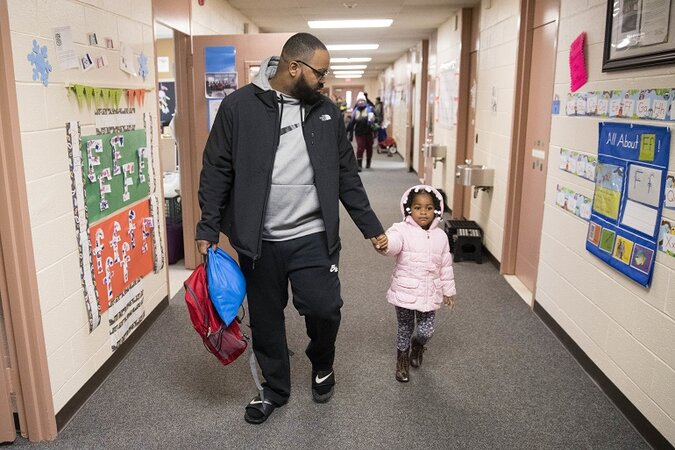 Father walking with his daughter in school.