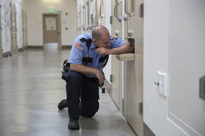 A corrections officer bends down to talk to a prisoner in a cell.