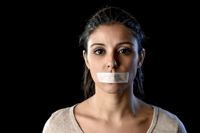 Woman with tape over her mouth.
