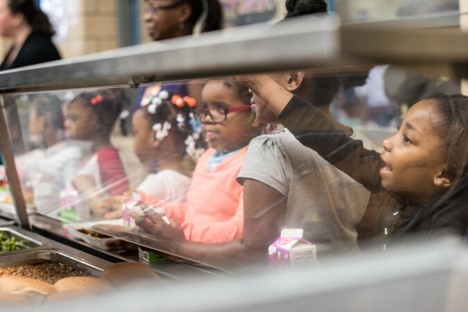 Children wait in line to be served at the school cafeteria.