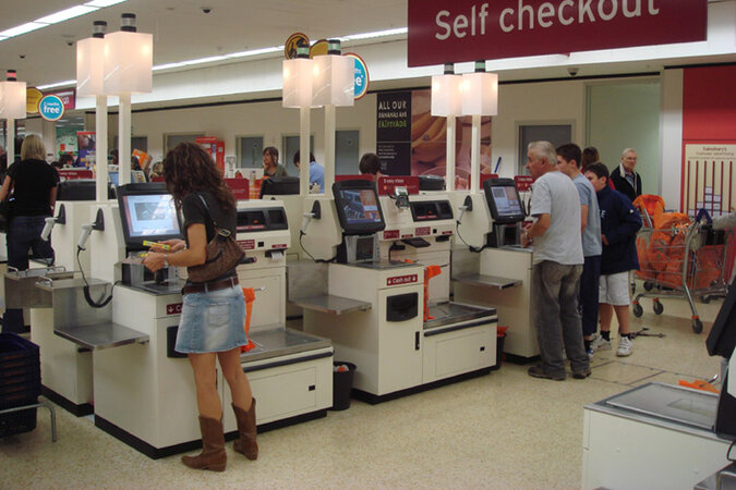 People using self checkouts at a store.