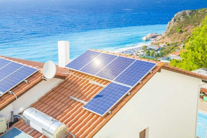 Solar panels on a home by the ocean.