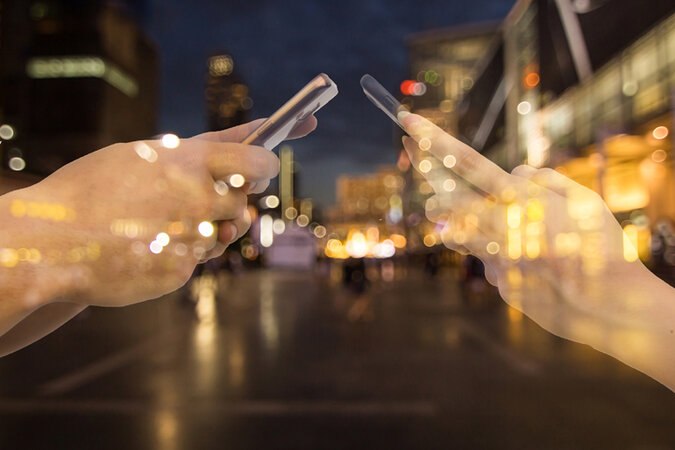 Hands on smartphones, superimposed over a cityscape