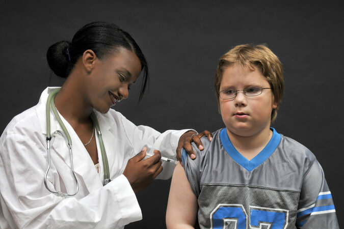 Boy receiving a vaccine from a female doctor.