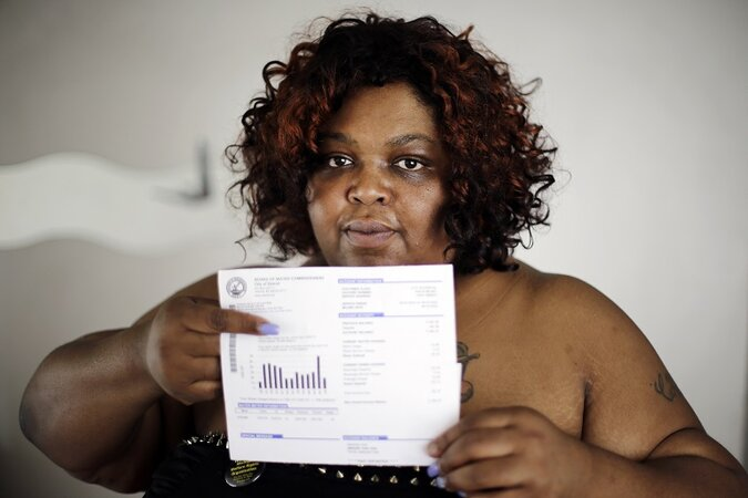 A Detroit resident holds up her past due water bill.