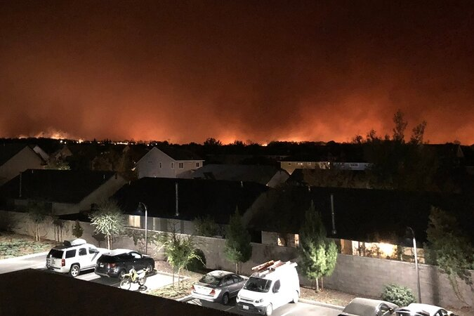 Wildfire in the distance of homes and cars.