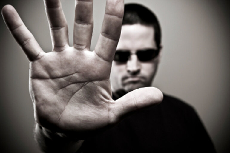 Man in sunglasses holding his hand up