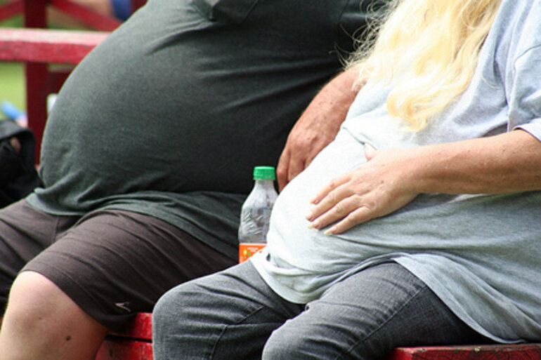 Two overweight people sitting