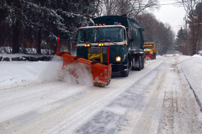 Two snow plows clearing a snowy road