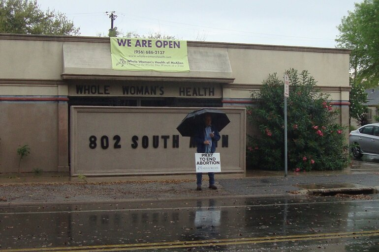 Abortion protester with umbrella standing outside of abortion clinic with sign.