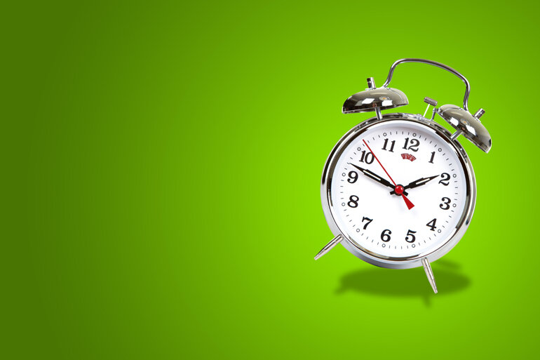 Alarm clock ringing on a green background.