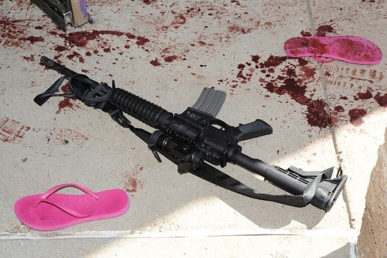 An assault rifle and blood-soaked sandals.