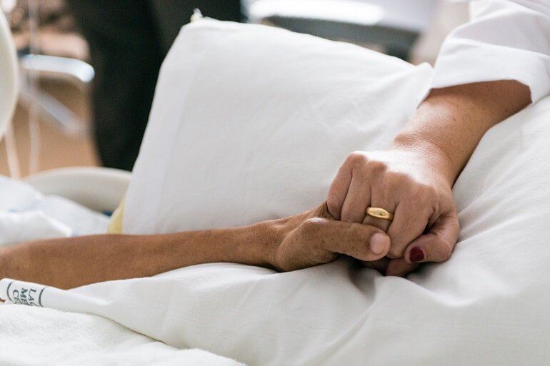 A doctor holds hands with a patient.