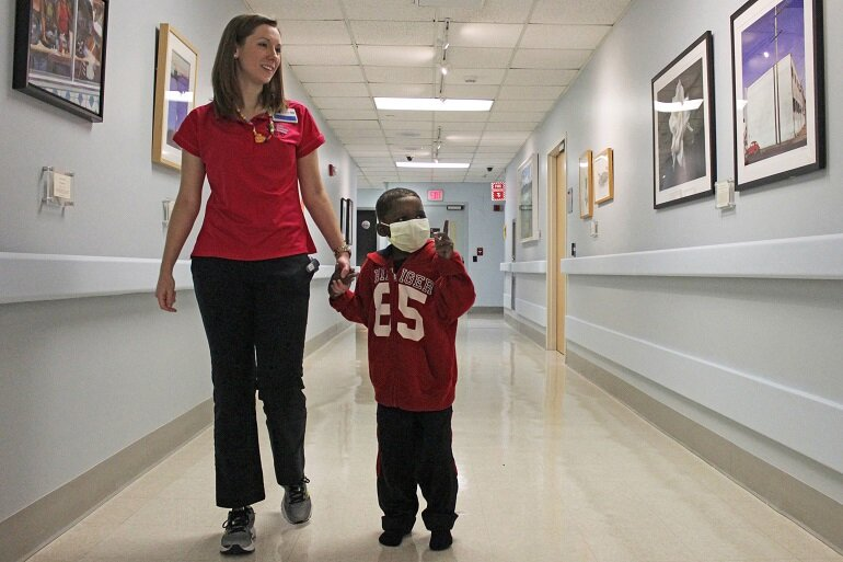 Nurse walking child through hospital hallway.