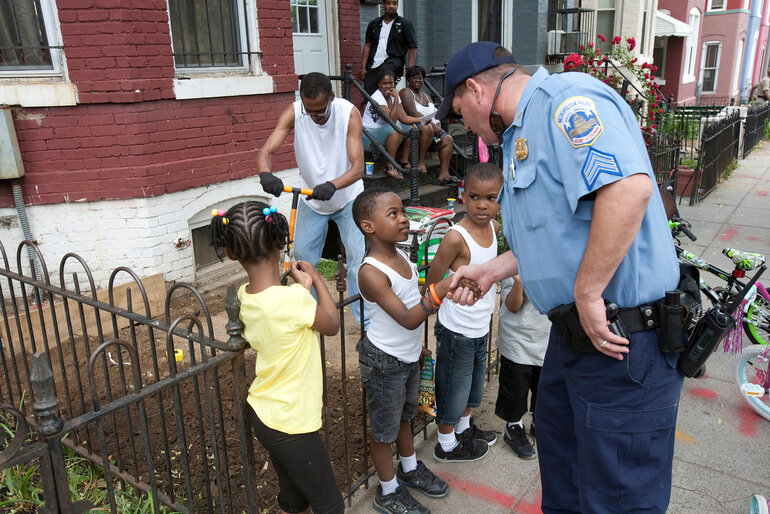 An officer shakes hands with a young boy in Washington, D.C., which has been a pioneer of community policing.