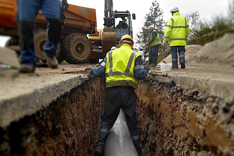 Construction workers digging into pipeline.