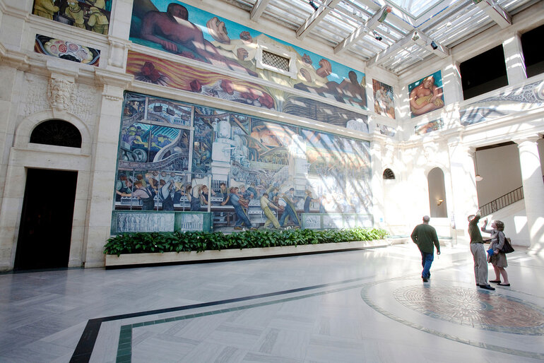 People survey a Diego Rivera painting at the Detroit Institute of Arts.