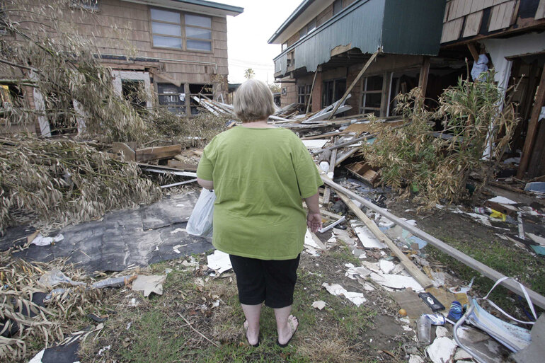Woman surveys hurricane damage of her home.