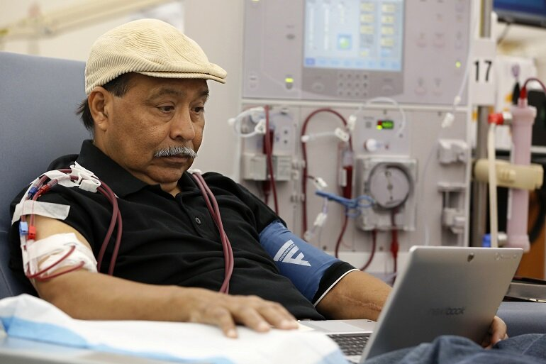 Man on a computer while getting dialysis.