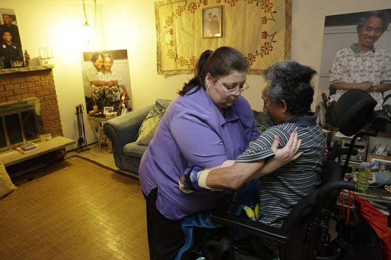 Home health care worker helps her client out of their wheelchair