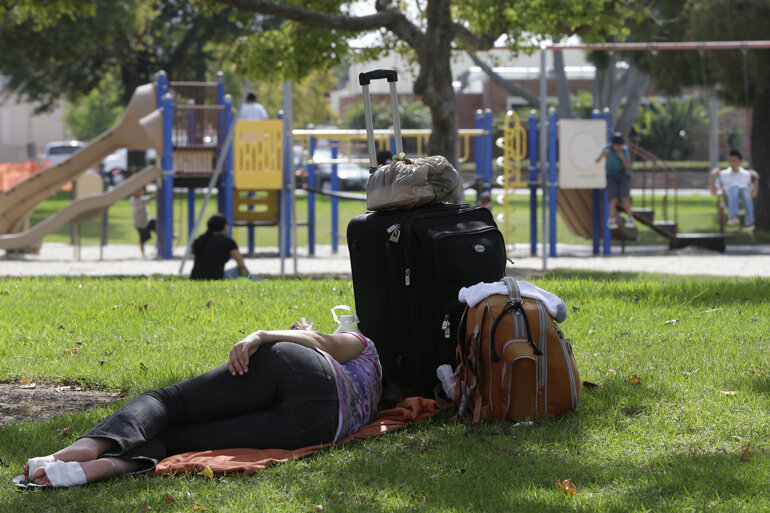 Homeless person sleeping near a playground.