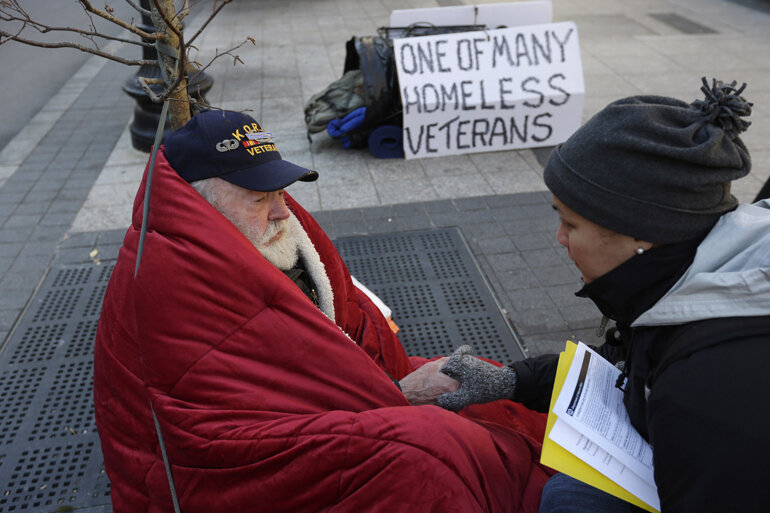 A woman helping a homeless veteran on the street.