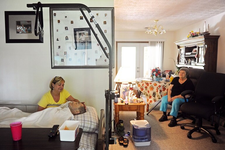 A home hospice patient rests in his bed in the living room.