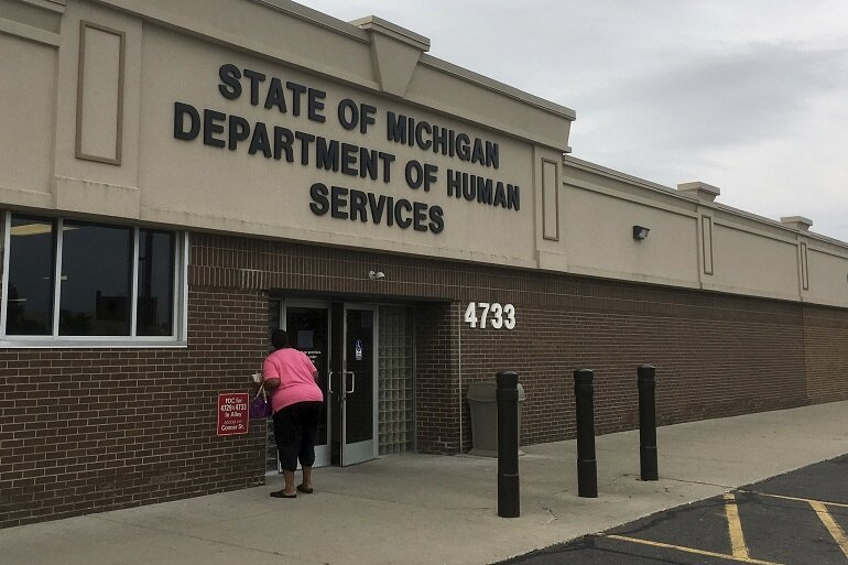 A woman enters a Michigan Department of Health and Human Services office.