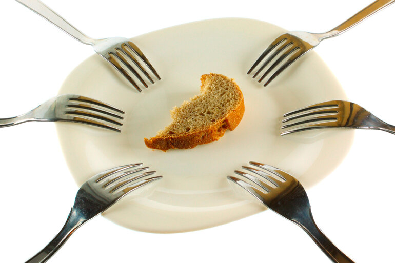 Piece of bread on a plate with a lot of forks.