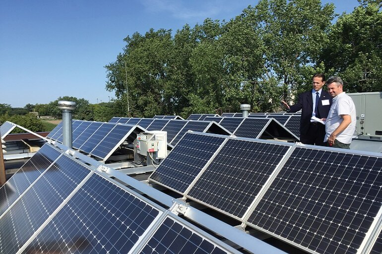 two men look over solar panels and discuss