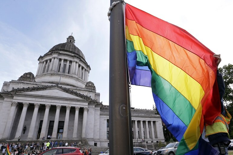 A state worker unfurls a rainbow flag in front of the Washington state Capitol.