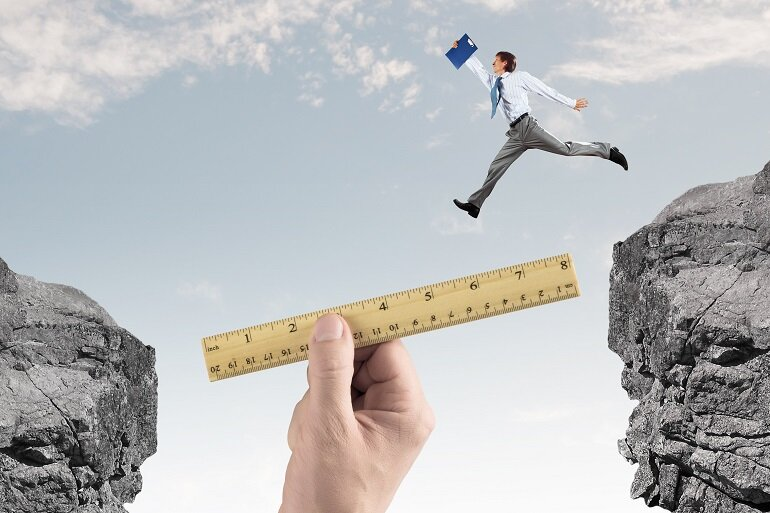 Man in suit jumping over gap filled with ruler