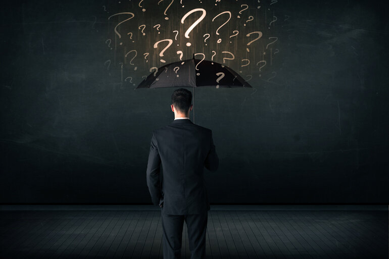 Man holding umbrella with question marks hovering above.