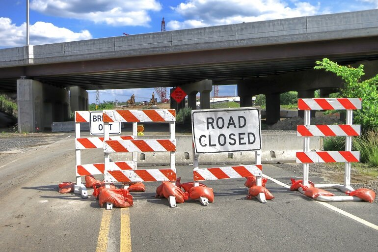 """A """"Road Closed"""" sign under a highway overpass."""