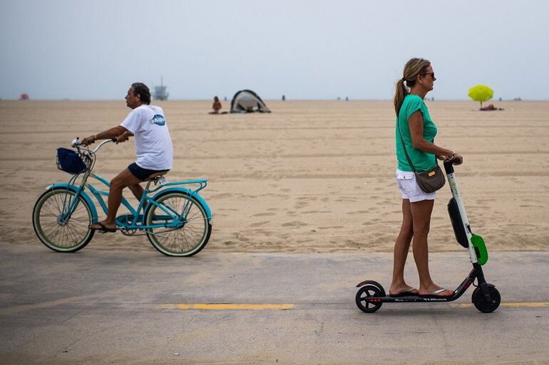 An electric scooter rider passes a cyclist on the Venice Beach Boardwalk.