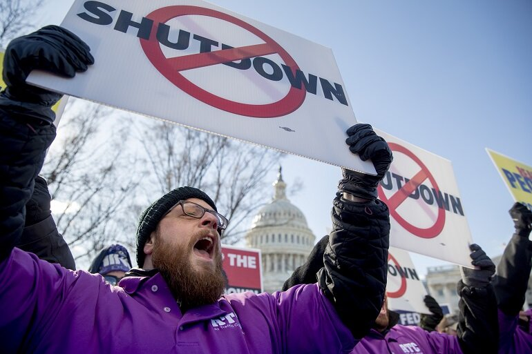 Man holding a sign and yelling outside the U.S. Capitol.