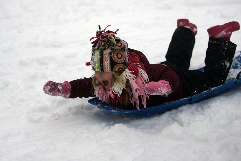 A child slides down a hill in Royal Oak, Mich., on a snow day that closed hundreds of schools through the region.