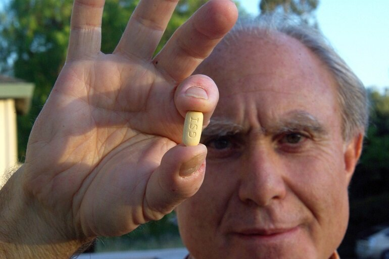 A hepatitis C patient holds Sovaldi, which costs $1,000 per pill, or $84,000 for a 12-week treatment course.
