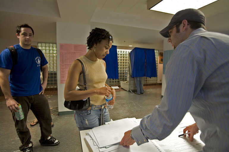 A poll worker checks a list of registered voters.
