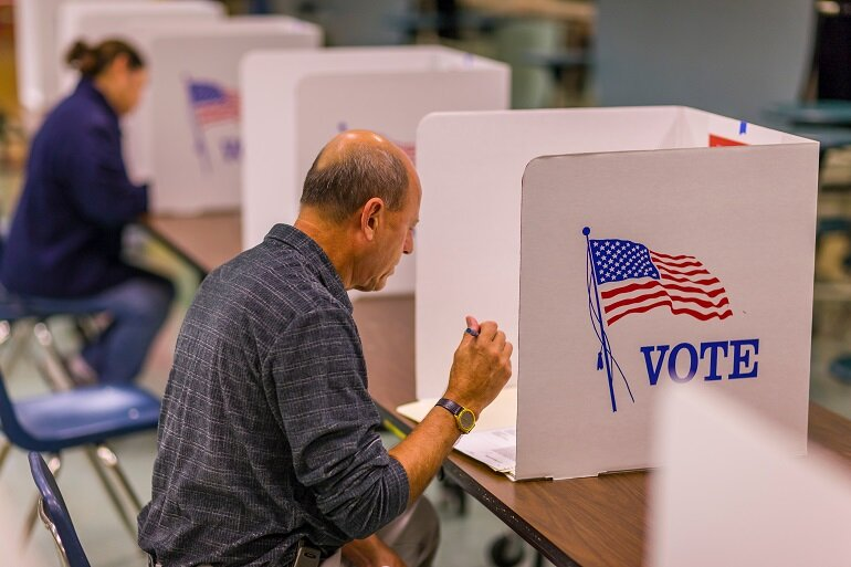 Man sitting down in a voting booth.