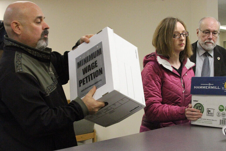 Members of the Alaska AFL-CIO, left, and Ed Flanagan delivering more than 43,000 signatures to put a measure to raise the minimum wage on the August ballot.
