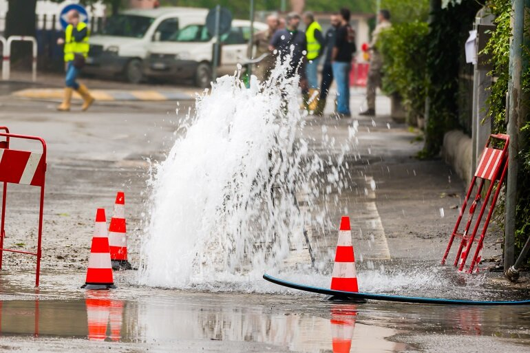 Workers addressing a water main break on a street with traffic cones.