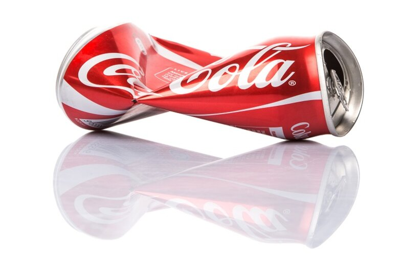 Crushed up coke can against a white background