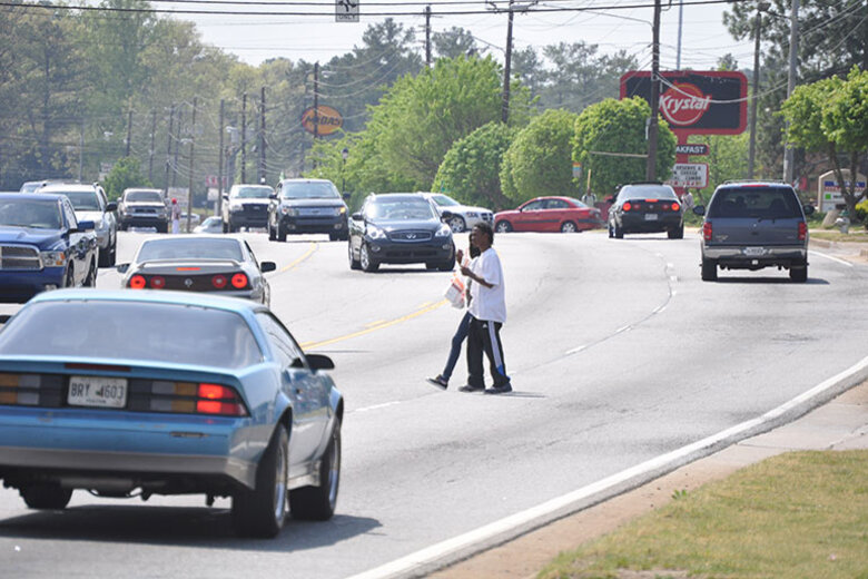 Pedestrians cross a busy stretch of highway in South Fulton County Ga.