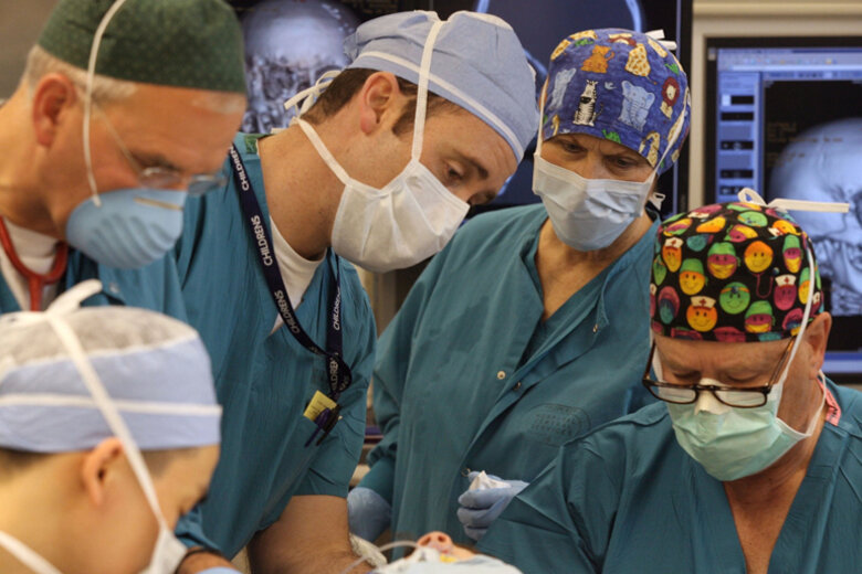 Surgeons and anesthesiologists (the highest-paid professions last year) performing a facial surgery at Seattle Children's Hospital.
