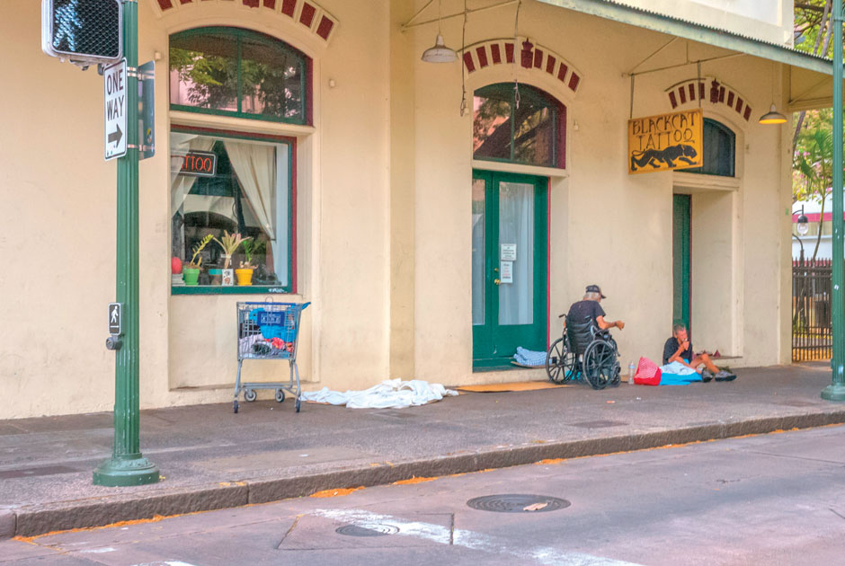Two+people+experiencing+homelessness%2C+one+in+a+wheelchair%2C+sit+outside+a+closed+tattoo+shop+on+a+sidewalk+in+Hawaii