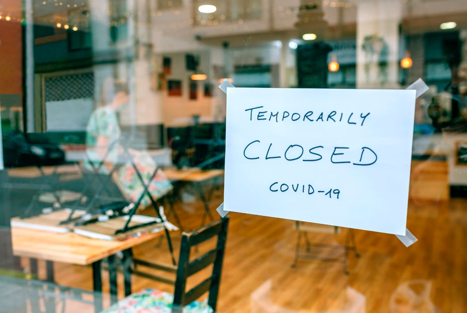 A+sign+taped+to+the+window+of+a+cafe+reads+%22temporarily+closed+COVID-19%22