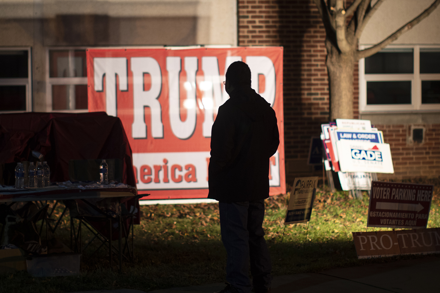A+silhouette+of+a+person+standing+in+front+of+a+Trump+campaign+sign.